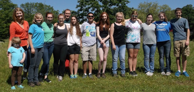A group of young people stand together outside in the grass with trees behind them.