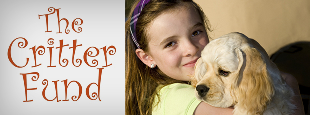 A girl smiles while holding a dog.