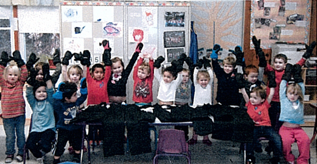 Students at Canaan Childcare Center stand together with their arms in the air while wearing ski-quality mittens.