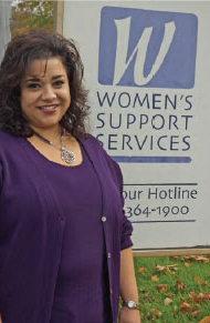 A woman in a purple dress stands in front of the Women's Support Services sign.